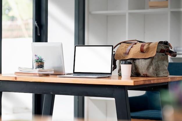 Mockup-laptop mit leerem bildschirm mit kaffeetasse und tragetasche auf holztisch im café-raum.