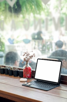 Mockup leere weiße bildschirmtablette mit magischer tastatur auf holztisch im café-raum.