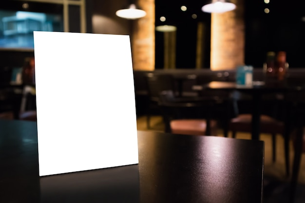Mockup leerer weißer etikettenmenürahmen auf tabelle mit innenhintergrund des caférestaurants