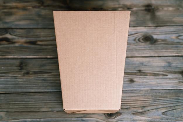 Mockup leeres handwerk brauner trapezförmiger karton auf einem alten holztisch hautnah. draufsicht, flache lage und platz für text