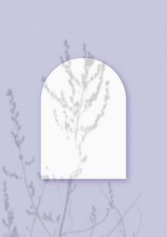 Mockup mit pflanzlichen schatten, die auf einem blatt in form eines bogens aus strukturiertem weißem papier auf violettem tischhintergrund überlagert sind. vertikale ausrichtung.