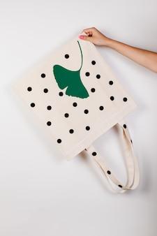 Mockup nahaufnahme einer wiederverwendbaren weißen tasche mit aufdruck von großen schwarzen erbsen und grünem blatt auf weiß isoliert...