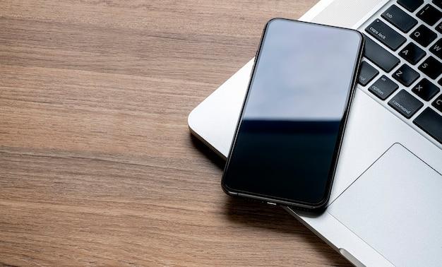 Mockup smartphone mit leerem bildschirm und laptop auf dem tisch.
