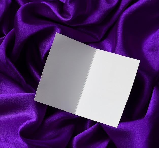 Mockup, szenenschöpfer. leere karte auf lila satinstoff öffnen, draufsicht. luxus stoff hintergrund.