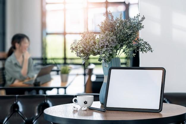 Mockup-tablette mit leerem bildschirm im café mit unscharfem hintergrund der jungen frau, die am tisch sitzt.