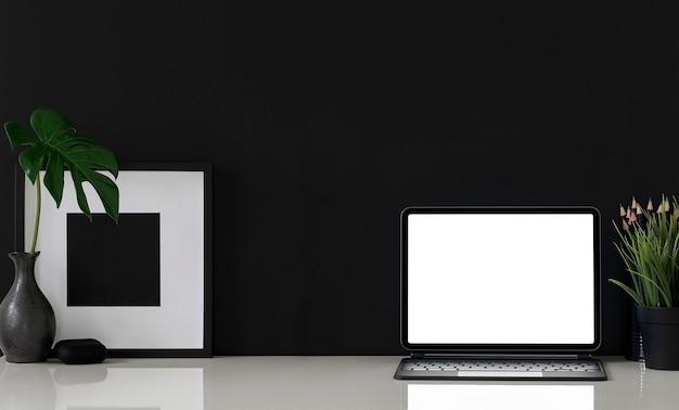 Mockup-tablette mit leerem bildschirm mit tastatur und schwarzem holzrahmen auf weißem tisch, schwarzer farbhintergrund.