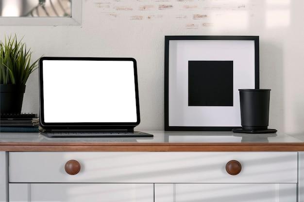 Mockup-tablette mit leerem bildschirm und magische tastatur, schwarzer holzrahmen und schwarze tasse auf holztisch im modernen raum.