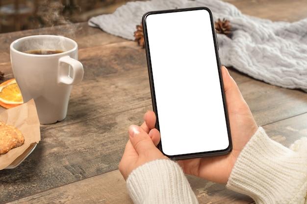 Mockup-telefon. hand der hand der handfrau, die sms mit handy auf schreibtisch am kaffeehaus hält