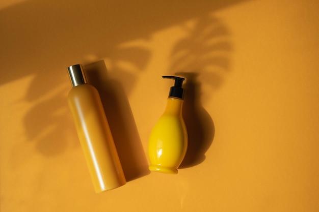 Mockup von gelben kosmetikflaschen mit schattenmonsterablättern auf gelbem hintergrund. eine kreative, minimalistische aufnahme eines kosmetikprodukts. das konzept des sommers, naturkosmetik. flach liegen.