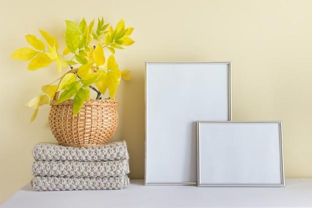 Mockup-vorlage mit zwei silbernen rahmen vertikal a4 und horizontal a5, gestrickter warmer herbstschal und herbstliche gelbe blätter im holzkorb.