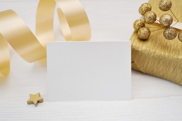 Mockup weihnachtsgrußkarte mit goldgeschenkband, flatlay auf einem weißen hölzernen hintergrund