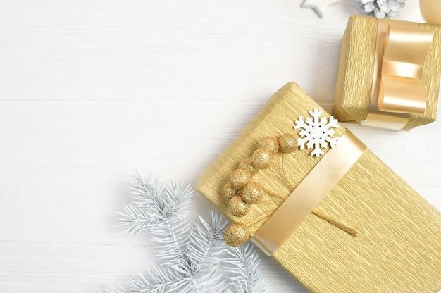 Mockup weihnachtsweißbaum, beige bogen, geschenkbox und kegel. flach lag auf einem weißen hölzernen hintergrund.