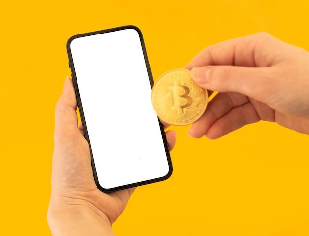 Mockup-zahlung mit bitcoin, gelber hintergrund, frau mit handy und goldener münze in den händen, platzfoto kopieren