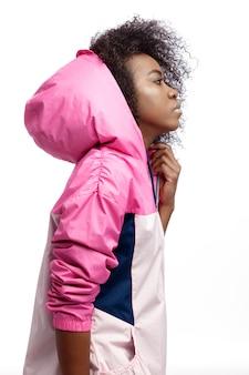 Mod junges lockiges braunhaariges mädchen, das in der rosafarbenen sportjacke mit kapuze gekleidet ist, posiert auf dem weißen hintergrund im studio.