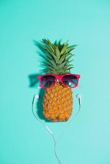 Mode ananas mit sonnenbrille und kopfhörer hört musik über blauem hintergrund