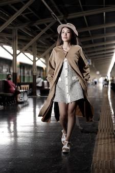 Mode asiatische frau tragen cremefarbenes luxusmantelkleid mit hut. junges modell fährt im sommer mit dem zug an der bahnhofsbahn. konzept nach post covid