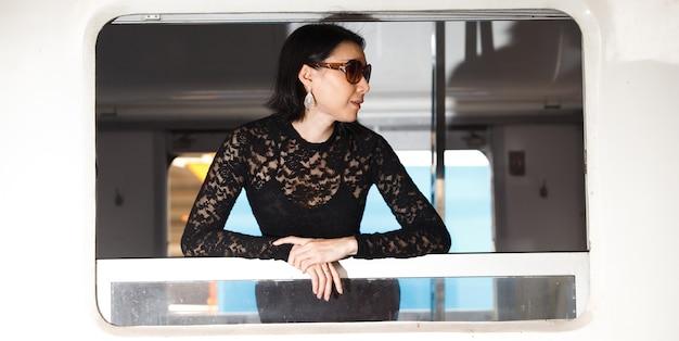 Mode asiatische frau tragen schwarzes luxus-spitzenkleid mit brille. das lgbt-transgender-modell fährt mit dem zug an der bahnhofsbahn.