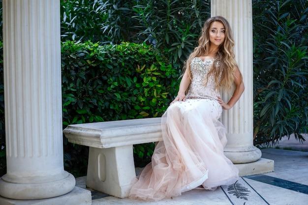 Mode-außenfoto der eleganten schönen frau mit den blonden haaren im luxuriösen paillettenkleid und in den silbernen accessoires, die im sommerpark aufwerfen