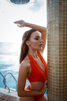 Mode-außenfoto der schönen sinnlichen frau mit langen dunklen haaren im eleganten orangefarbenen badeanzug, der neben schwimmbad entspannt