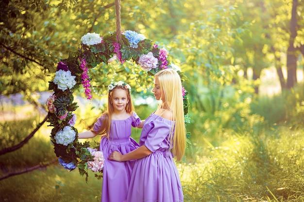 Mode-außenfoto des schönen familienlooks. schöne mutter mit langen dunklen haaren posiert mit ihrem kleinen süßen baby in ähnlichen kleidern mit blumendruck