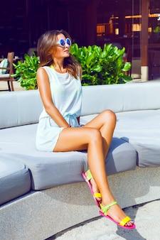 Mode-außenporträt der hübschen braunen sportlichen frau entspannte sich und genoss sonnigen heißen tag in ihrem urlaub auf luxusresort, lässiges strandkleid und sonnenbrille tragend. helle sonnige farben.