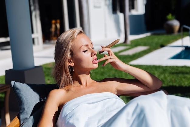 Mode-außenporträt der nackten frau sitzt auf sofa, das sich mit decke bedeckt, die zigarre hält