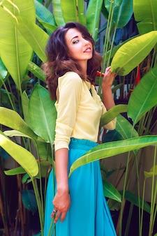 Mode-außenporträt der sinnlich schönen brünetten frau, mit erstaunlich langen haaren jedes helle make-up, posierend in der nähe von exotischen pflanzen am sommertag, tragend luxuriöses helles seidenkleid und halskette.