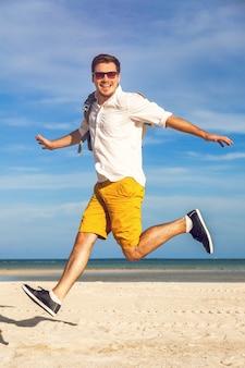 Mode-außenporträt des gutaussehenden mannes im hellen trendigen lässigen outfit, das am tropischen strand geht
