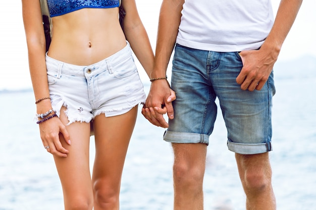 Mode-außenporträt des jungen mannes, der hand ihrer freundin hält, junges hipster-paar in der liebe genießen reisen im sommer zusammen, das am meer aufwirft.