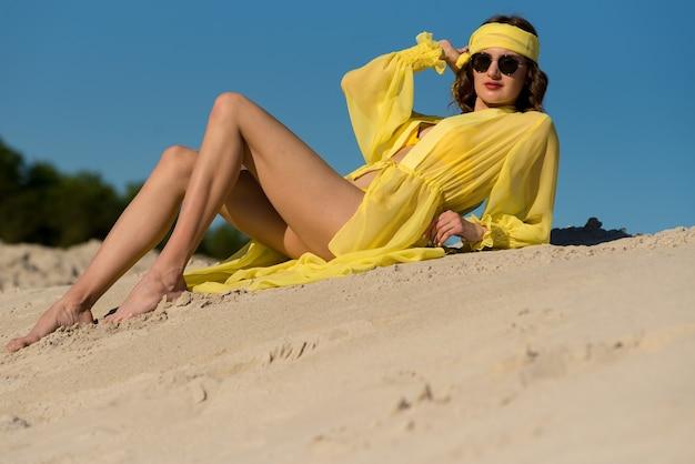 Mode-badeanzug-bikini-frau in heißen badebekleidung, die auf luxusreise-urlaubsstrandziel geht