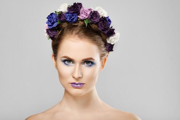 Mode beauty model mädchen mit blumen im haar. perfektes kreatives make-up und frisur für blumenkunst.