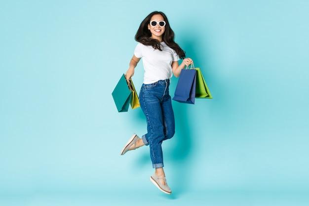 Mode-, beauty- und lifestyle-konzept. sorgloses attraktives und glückliches asiatisches mädchen in der sonnenbrille, vom glück nach dem einkaufen springend, taschen mit kleidern haltend, hellblaue wand stehend