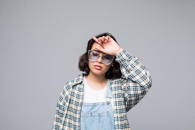 Mode brünette frau in kleid und sonnenbrille posiert in der isolierten weißen wand