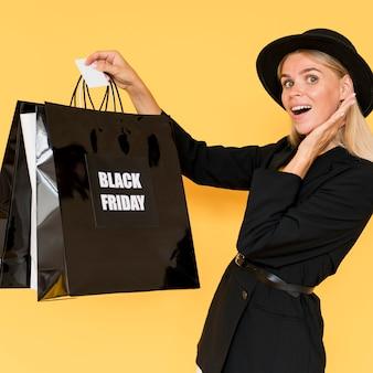 Mode dame, die schwarze kleidung trägt, die schwarze freitags-tasche hält