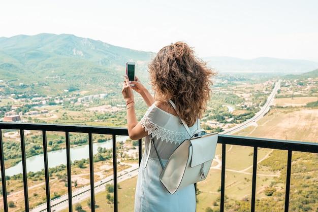 Mode der brünetten frau des jungen mädchens machen panoramablick am telefon. porträt der jungen schönen frau, die die alte stadt geht. lifestyle, reisen, urlaub, tourismus