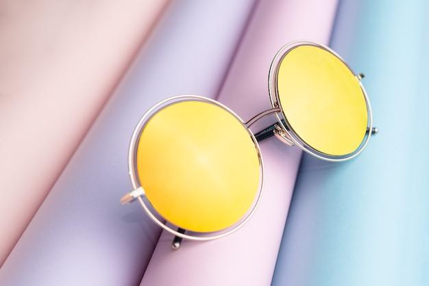 Mode der sonnenbrille mit gelber linse auf buntem papierhintergrund