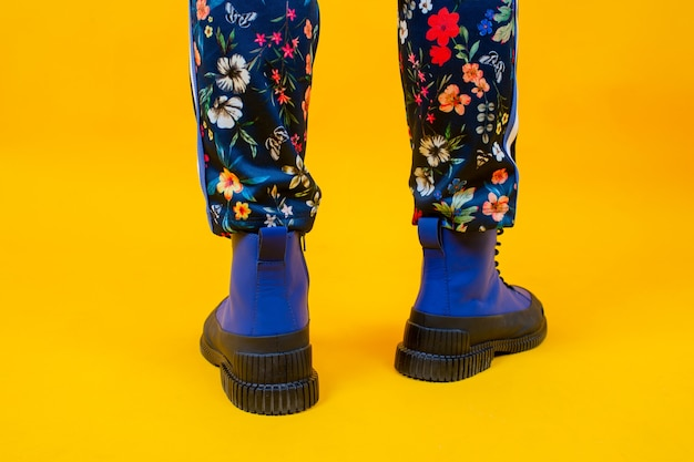 Mode frauenbeine in bunten hosen und blauen stiefeln
