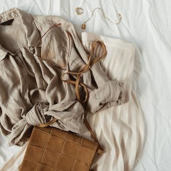 Mode frauenkomposition mit schönen stilvollen kleidern und bijouterie. rock, bluse, geldbörse, ringe, halskette auf weißer leinendecke. flach liegen