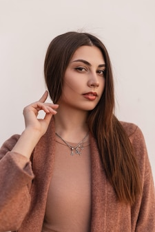 Mode frisches porträt schöne hübsche junge frau mit sexy lippen mit natürlichem make-up mit langen braunen haaren im eleganten mantel. sinnliches nettes mädchenmodell, das draußen nahe weißer wand aufwirft.