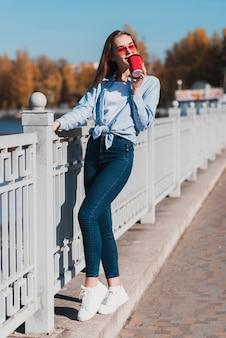 Mode gekleidete frau, die einen tasse kaffee hält