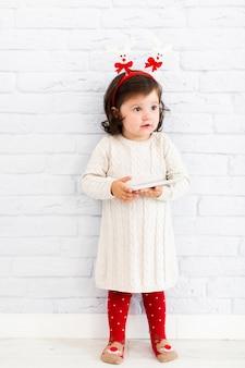 Mode gekleidetes kleines mädchen, das telefon hält