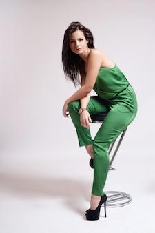 Mode gekleidetes sexy mädchen, das auf stuhl sitzt