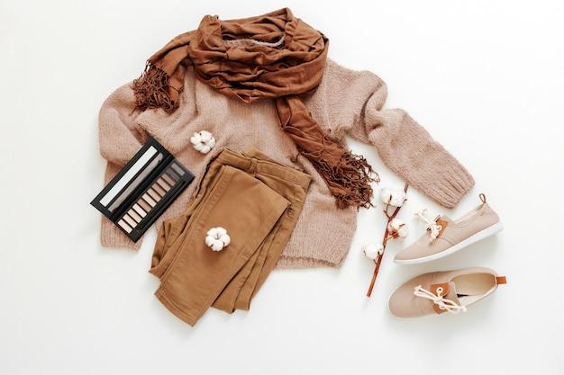 Mode grundlegende weibliche kleidung schuhe beige braune farben strickpullover schal baumwolle blumen kosmetik. flache lage frühlingswinterfrauenfrauenausstattung. freizeitkleidung eingestellt.