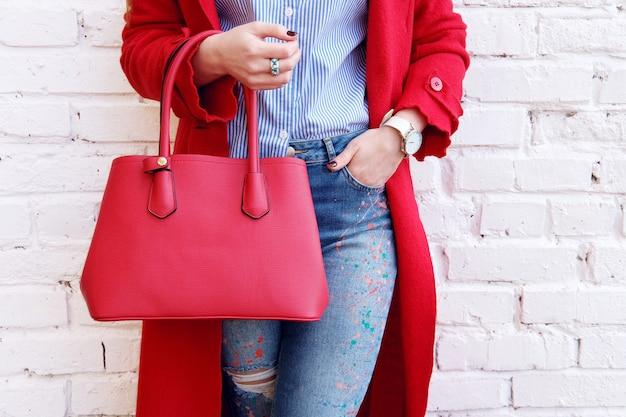 Mode-herbst-outfit-frau, die im roten mantel mit ledertasche nahe weißer wand aufwirft. stilvolles trendiges accessoire