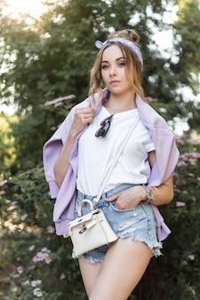 Mode-hipster-frau mit vintage-bandana in zerrissenen jeans-shorts und weißem t-shirt mit lederhandtasche posiert in der nähe von blumen im freien