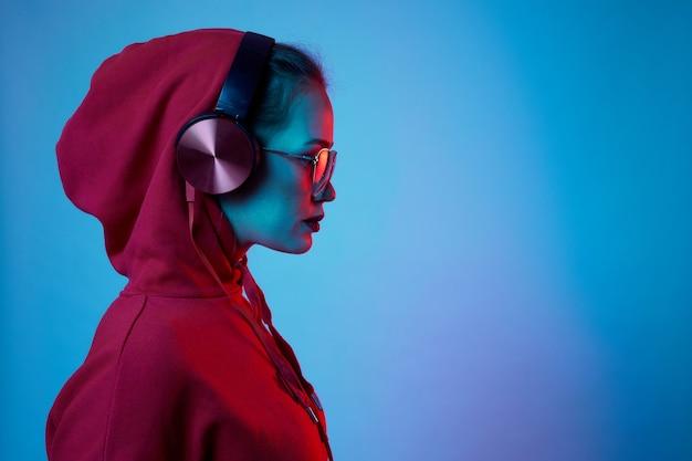 Mode-hipster-frau tragen stilvolle brille und kopfhörer, die musik über farbneonhintergrund im studio hören.