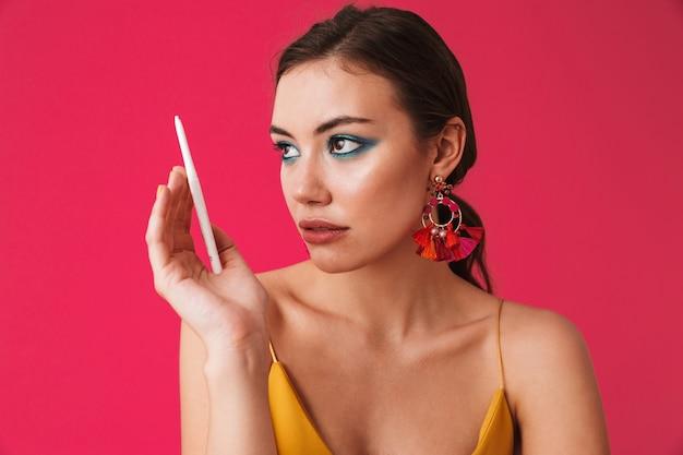 Mode hübsche frau, die ohrringe trägt, die beiseite schauen und weißen stift für make-up halten