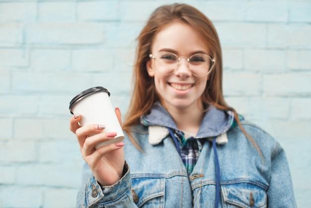 Mode hübsche frau mit kaffeetasse in bunten kleidern über weiß, die eine rosa hut gelbe sonnenbrille blaue jacke trägt