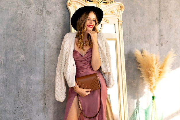 Mode-innenporträt einer schönen glamour-frau, die am sonnigen tag in der nähe einer grauen wand posiert und ein seidenkleid, eine warme strickjacke und einen schwarzen hut trägt