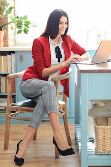 Mode junge brünette frau, die von zu hause mit laptop arbeitet. telearbeitskonzept